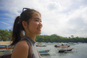 happy Asian Chinese woman with backpack in beach trip tourist excursion smiling sweet in Summer holiday and vacation travel