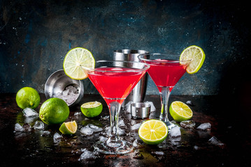 Red cosmopolitan cocktail with lime in martini glass, on dark rusty background copy space