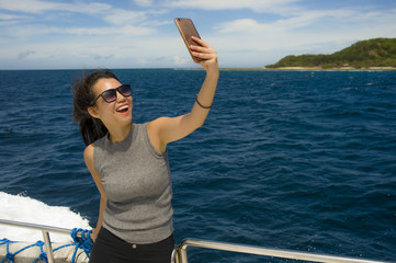 young attractive and happy Asian Chinese woman selfie portrait picture with mobile phone on boat or ferry smiling with blue sea background