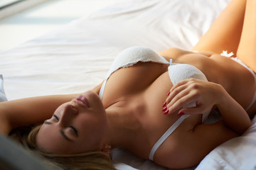 Sensual woman in bed. Sexy girl in white bra.