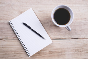Top view Note book with pen and a cup of coffee on wood table for Business