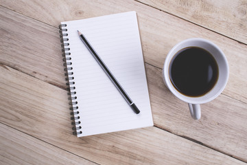 Top view Note book with pencil and a cup of coffee on wood table for Business