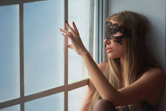 Woman looking out the window. Sad girl in lace mask.