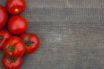 Several juicy red tomatoes on a wooden background.