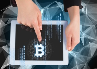 Bitcoin icon and interface on tablet in hands