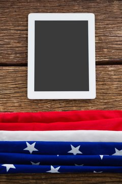 American flag and digital tablet arranged on wooden table