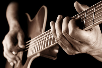 guitarist playing country guitar, sepia image