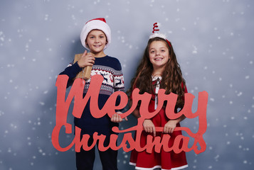 Portrait of siblings with christmas ornament among snow falling