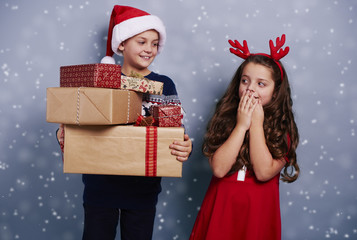 Happy siblings with stack of gifts among snow falling