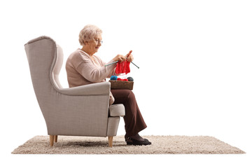 Senior lady sitting in an armchair and knitting