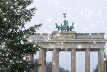 Bradenburg Gate with Christmas tree at winter day with falling snow, Berlin, Germany