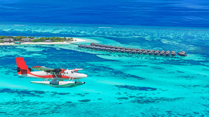 Maldives island aerial landscape view.  Beautiful blue sea and luxury water villas. Seaplane aerial view of Maldives atoll and coral reef