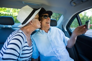 Senior man taking selfie with woman in car