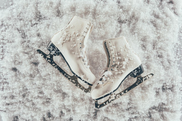 top view of pair of white skates under snow