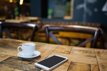 Close up of mobile phone and tea cup on table