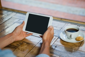 Cropped image of man holding tablet computer by coffee cup