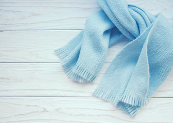 Light blue scarf tied up on a wooden background (copy space on the left), retro style
