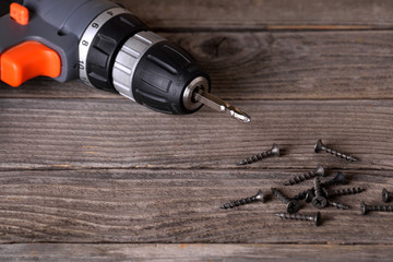 Close up Electric drill on wooden table background and copy space.  Hammer drill or screwdriver, Electric cordless hand drill on wooden. maintenance home concept. Screwdriver on a wooden background wi