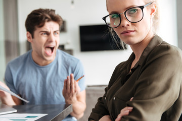 Young blonde lady looking camera while her man scream at her
