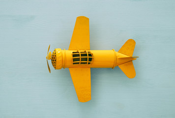 Top view image of retro yellow metal toy airplane over blue background.