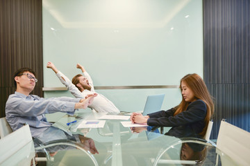 Group of business people stretching in meeting room with blank picture