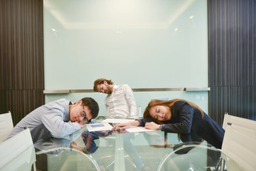 Group of business people sleeping in meeting room with blank picture