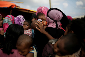A woman calms a baby as Rohingya refugees line up for a food supply distribution at the Kutupalong refugee camp near Cox's Bazar