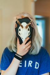 Woman closing face with skull