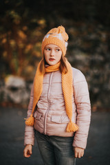 Outdoor portrait of pretty 10 year old girl wearing pink jacket and set of knitted hat and scarf