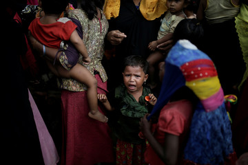 A baby cries as Rohingya refugees line up for a food supply distribution at the Kutupalong refugee camp near Cox's Bazar