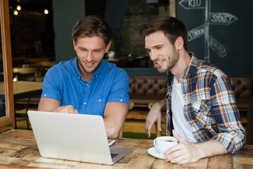 Smiling friends using laptop while sitting at table