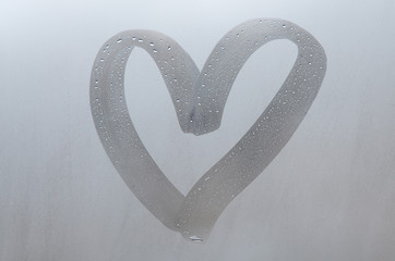 Autumn rain, the inscription on the sweaty glass - love and heart. Soft and beautiful background image with copy space
