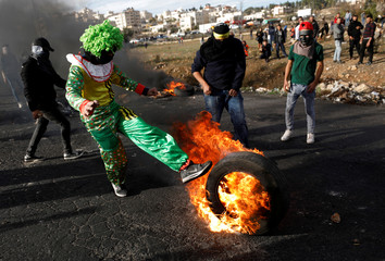 A Palestinian kicks a burning tire during clashes with Israeli troops near the Jewish settlement of Beit El near the West Bank city of Ramallah