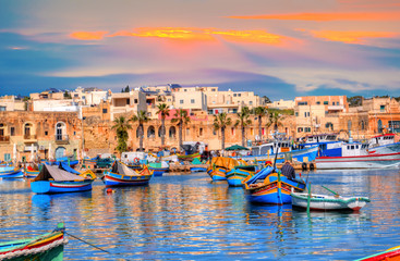 Marsaxlokk village port of Malta, illuminate by sunset light, European travel in beautiful place Wall mural