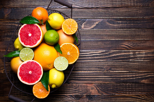Fresh citrus fruits in basket. Orange, grapefruit, lemon, lime, tangerine on dark wooden table. Assorted fresh citrus fruits with leaves. Top view and copy space