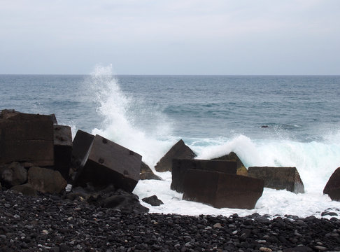 waves breaking over concrete cubic sea defenses in tenerife with white surf