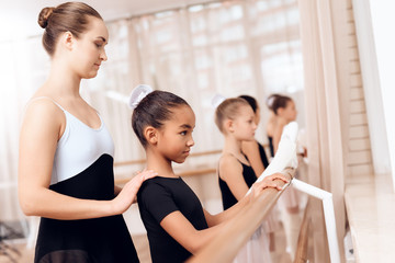Photo sur Toile Ecole de Yoga The trainer of the ballet school helps young ballerinas perform different choreographic exercises.