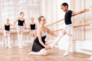 The trainer of the ballet school helps young ballerina perform different choreographic exercises.