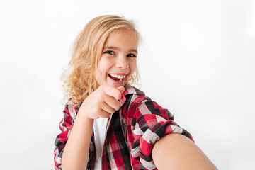 Portrait of a cheery little girl pointing finger at camera