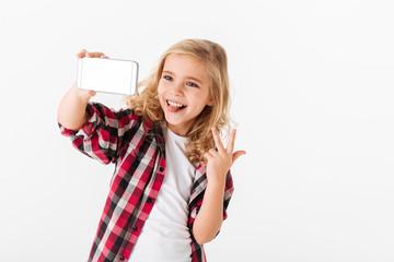 Portrait of a cheerful little girl taking a selfie