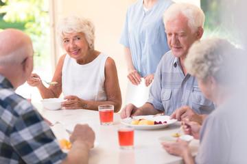 Smiling senior woman eating soup