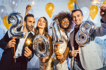 Party people women and men celebrating new years eve 2018 with sparklers and Champagne