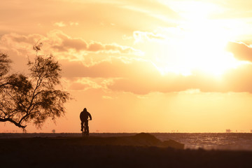 Man Cycling at Pebble Sea Beach at Sunset Silhouette