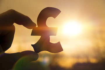 silhouette symbol of the British pound sterling in hand against the background of the dawn