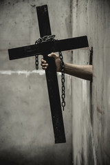 Black cross with a looped chain. And held by the hands of men who emerged from a hole in the old wall.