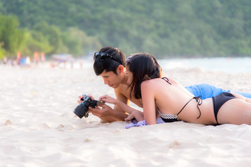 Couple enjoy and happy fun on beach laughing together looking at summer vacation travel photo pictures on retro vintage camera. Honeymoon relax together cozy.  Valentine, Summer Concept