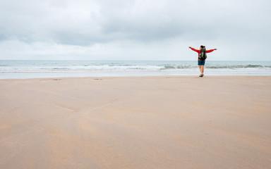 Woman backpaker traveler listen energy and power of ocean waves