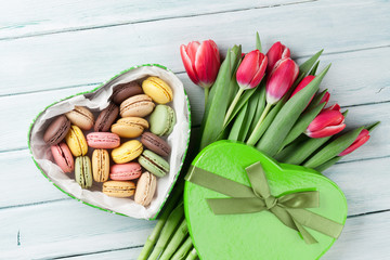 Red tulips bouquet and gift box with macaroons