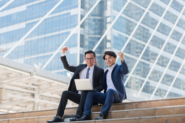 Asian two businessman happy while siting see laptop. in the business district background