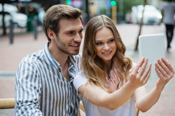 Happy couple holding digital tablet while sitting at sidewalk